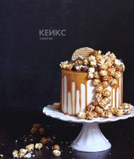 Белый торт с глазурью и попкорном Фото